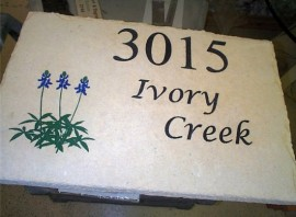 Curbside address stone with bluebonnets